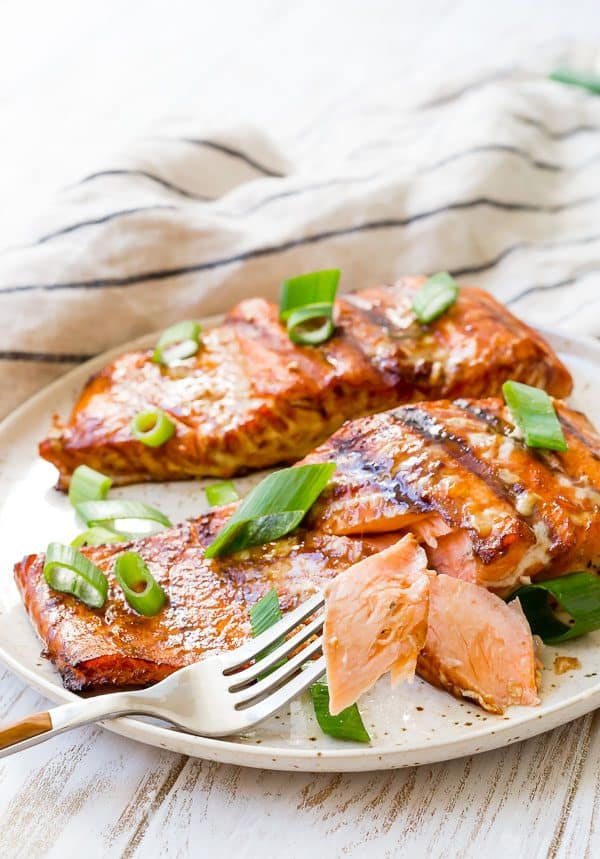 Salmon on a plate with a piece on a fork to show the flakiness and light pink/orange color of the salmon.