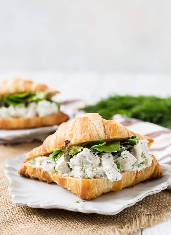 Chicken salad flecked with dill on a croissant with greens. It s placed on a fancy plate on a piece of burlap.