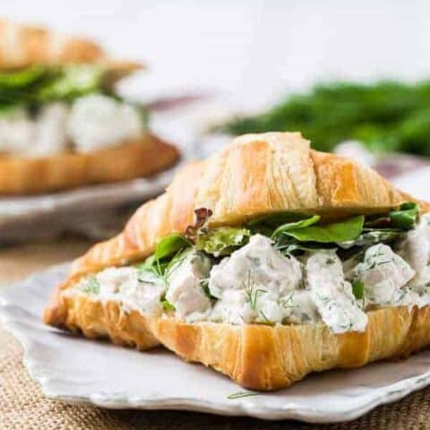 Chicken mixed with yogurt and dill on a split open croissant with greens.