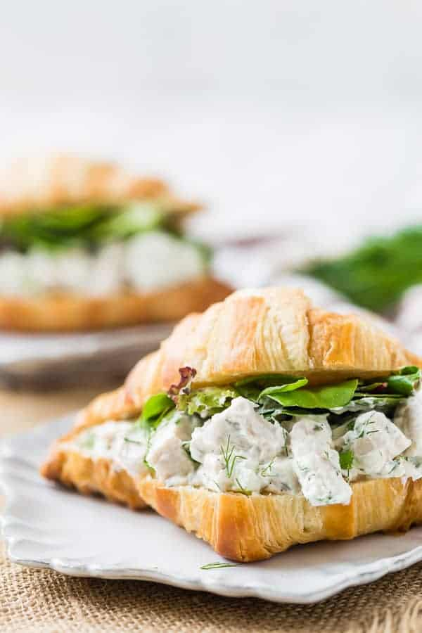 Dill chicken salad on a croissant with greens on a white plate.