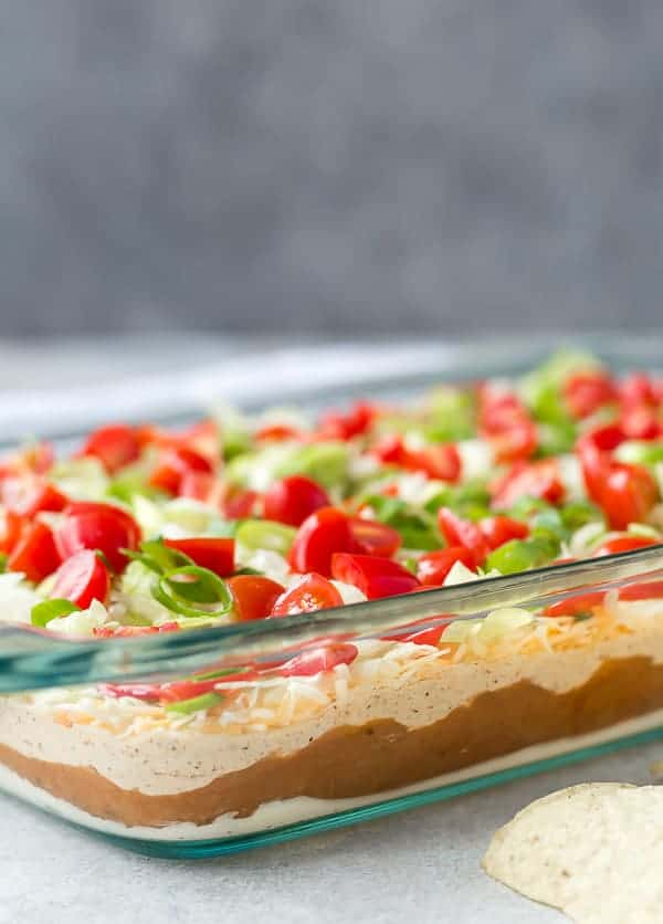 Close up view of a layered dip in a clear glass pan.