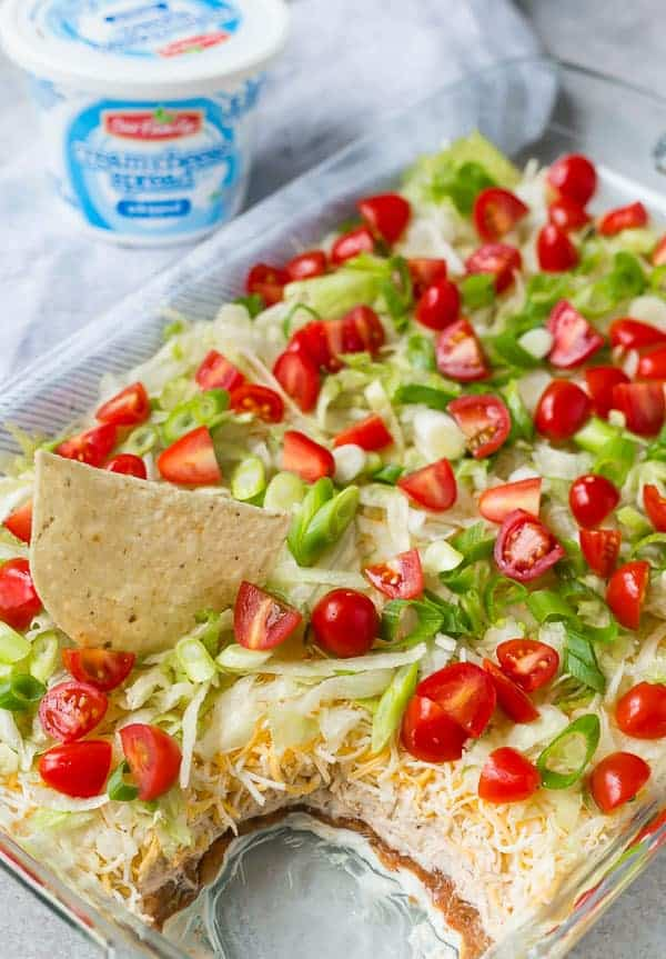 Clear glass 9x13 rectangular pan with layers of cream cheese, beans, cheese, tomatoes, green onions, and lettuce. A scoop is removed to show the layers.