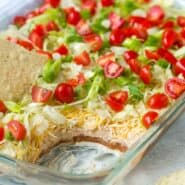 7 layer dip with scoop out to show the layers, chip dipped in the top.