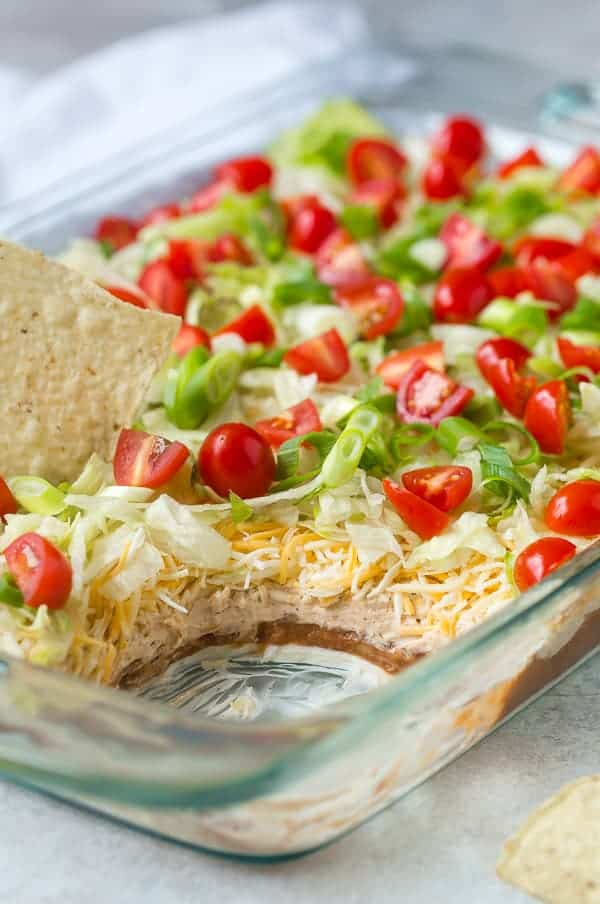 Close up view of a layered dip with beans, cream cheese, cheese, lettuce, tomatoes, and green onions.
