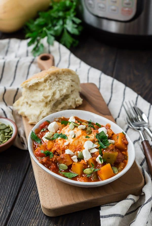 image of fall inspired instant pot shakshuka with bread, parsley, and squash in the background