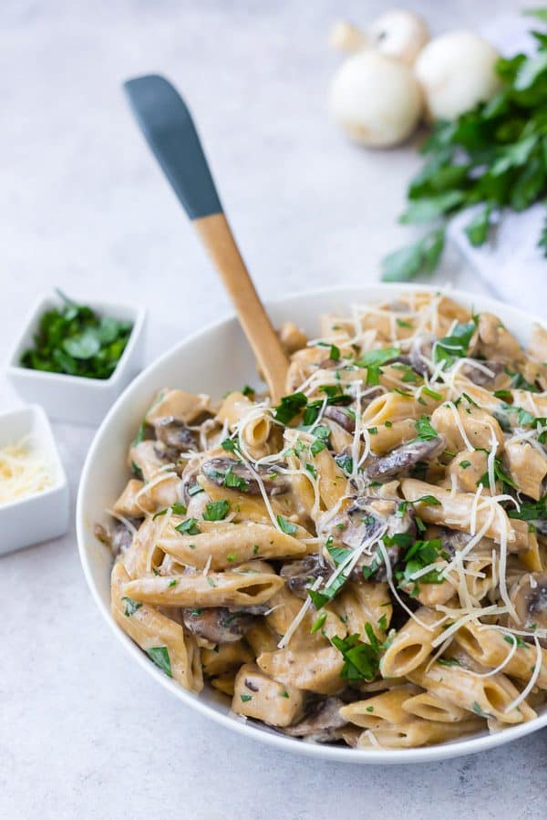 image of chicken marsala pasta in a creamy sauce in a white bowl with a wooden spoon