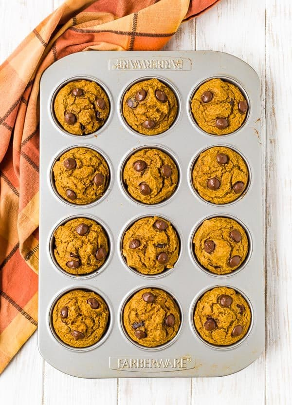 Overhead view of a 12-cup muffin tin filled with orange colored muffins sprinkled with chocolate chips.