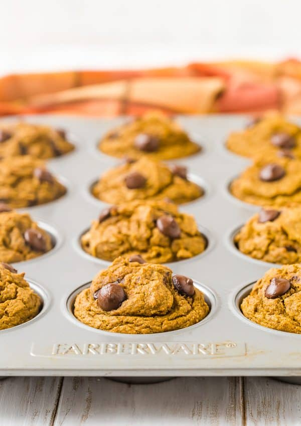 A muffin pan full of pumpkin muffins flecked with chocolate chips. Orange fabric is pictured in the background.