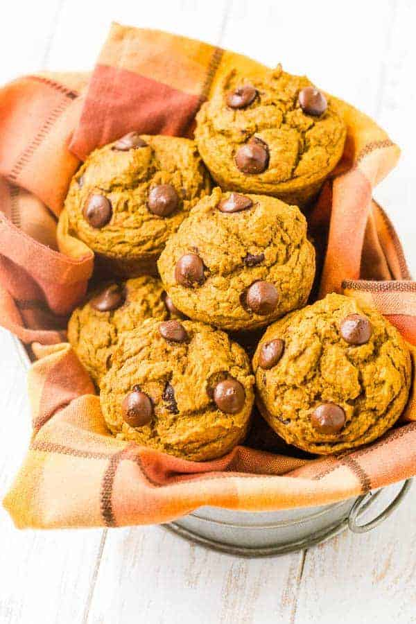 Pumpkin chocolate chip muffins in a basket with orange towel.