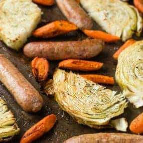 image of sausage, cabbage slices, and carrots on a sheet pan, sprinkled with dill