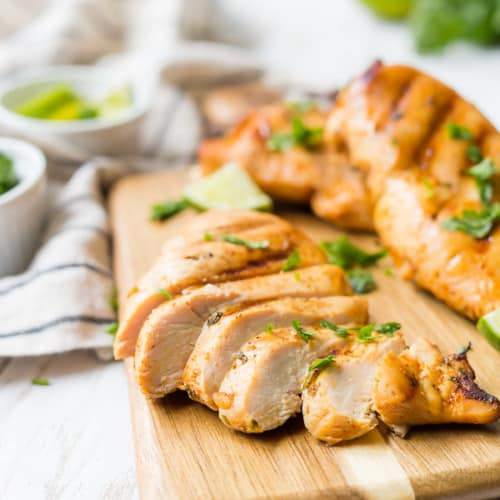 Grilled chicken breasts on a wooden cutting board. Chicken breast in the foreground is sliced.