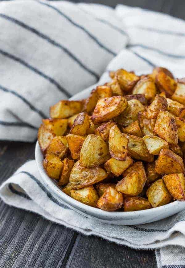 Small white bowl filled to the brim with small golden brown cuts of potato.