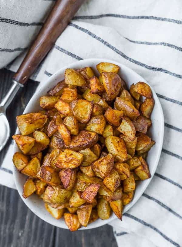 Overhead view of a oval white bowl filled to the brim with golden brown roasted potatoes.