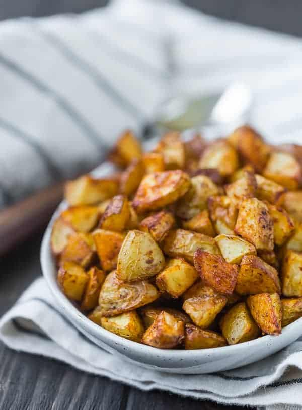 Close up view of small pieces of roasted potatoes in a small oval shaped white bowl.