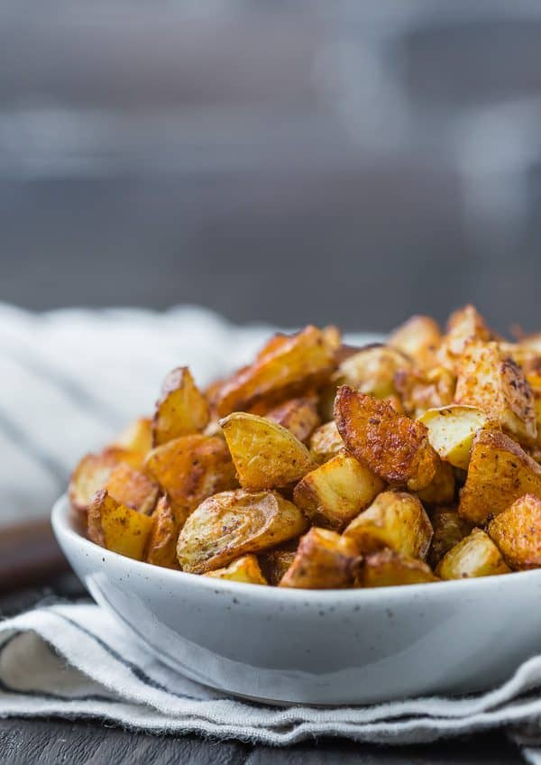 Close up view of roasted potatoes that are golden brown in color, placed in a small white bowl.