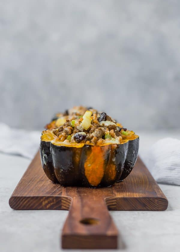 Acorn squash half filled with farro, sausage, dried cranberries, apples, and cheese on a wooden cutting board.