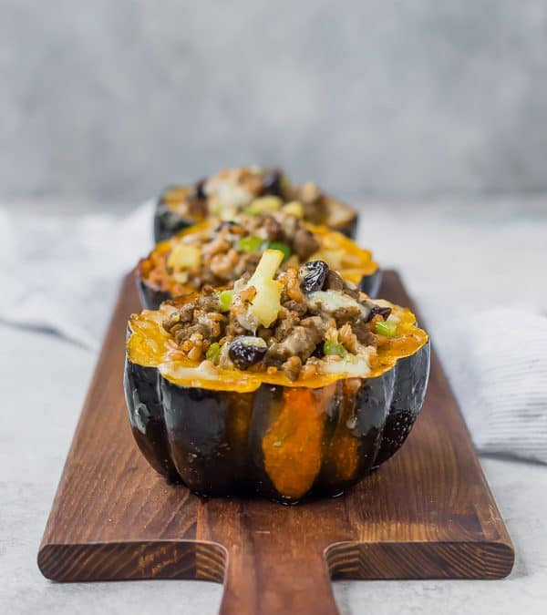 Three acorn squash halves on a wooden cutting board filled with farro, sausage, dried cranberries, apples, and cheese.