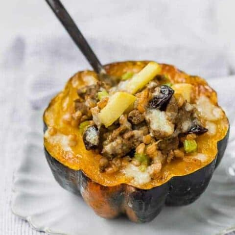 Acorn squash half on a white plate. Squash is filled with farro, sausage, apples, cranberries, and cheese.