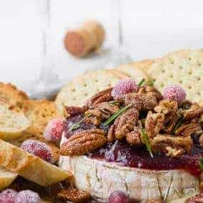 Image of Baked Brie Recipe with Cranberries and Candied Pecans with Bourbon. Garnished with sugared cranberries and rosemary.