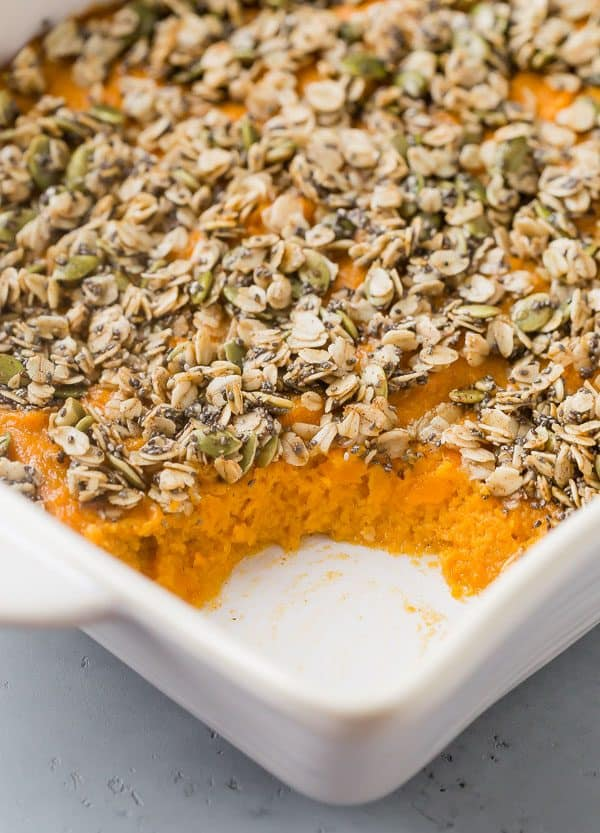 White baking dish filled with a sweet potato casserole topped with oats and pumpkin seeds. A scoop is removed to show creamy texture.