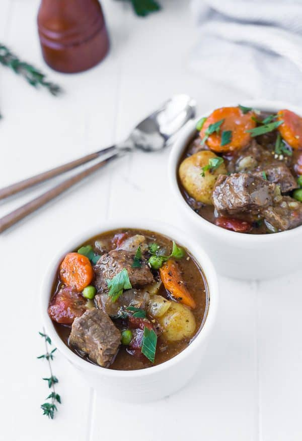 Image of Beef Stew in small white bowls, spoons in background, garnished with thyme sprigs
