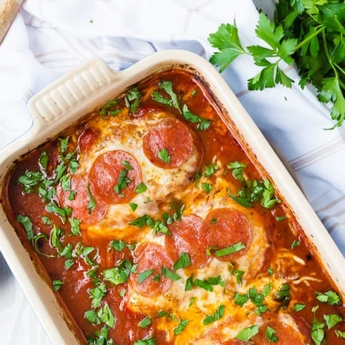 image of chicken topped with cheese and pepperoni in a baking dish