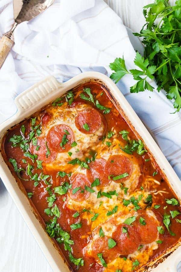 image of pizza chicken topped with cheese and pepperoni in a baking dish