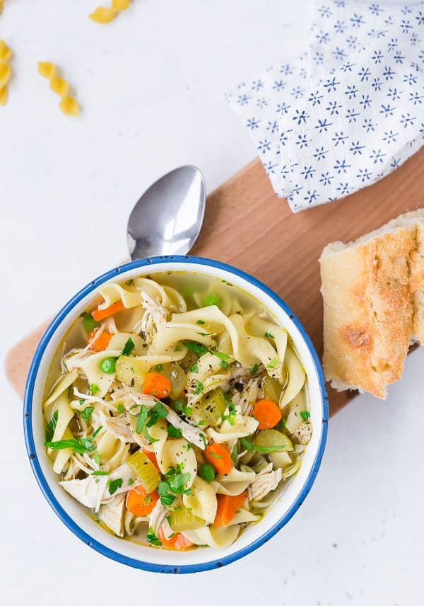 Image of Chicken Noodle Soup with spoon, bread. Overhead view of instant pot chicken noodle soup.