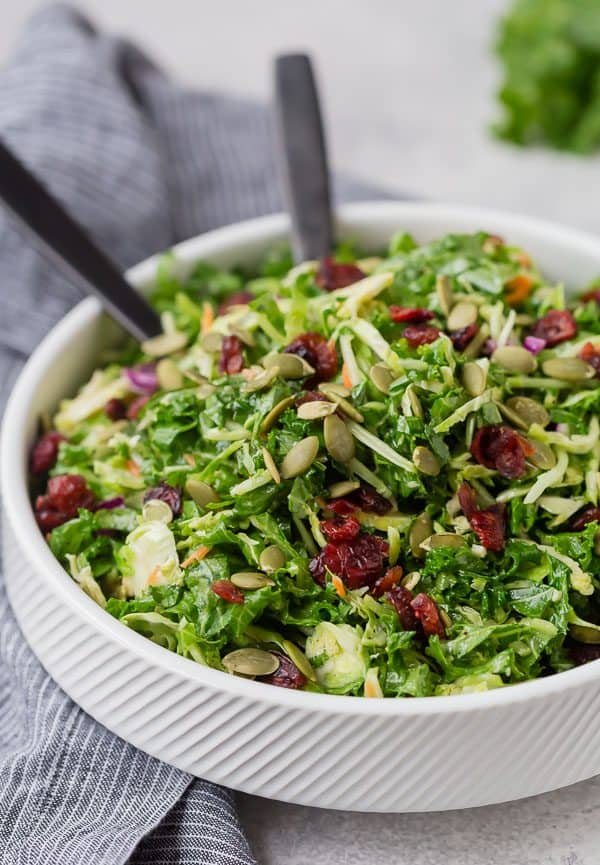 Image of sweet kale salad topped with dried cranberries in a white bowl with black serving utensils.