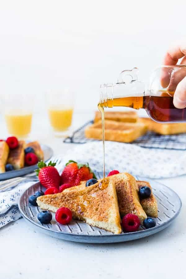Classic french toast with syrup being poured on top of it