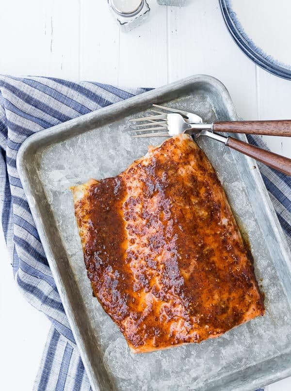 This easy five ingredient baked salmon is going to be your weeknight go-to salmon recipe. The glaze is the perfect balance of spicy and sweet. Try it tonight!