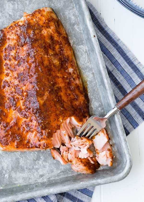 Image of baked salmon on a sheet pan, flaked with a fork. Image photographed from above. Blue towel in background.