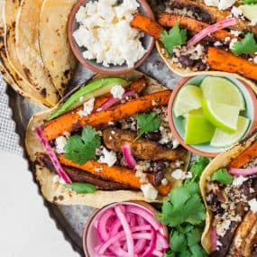 Image of colorful vegan tacos, shot from above with pickled onions, cilantro, avocado, and lime.