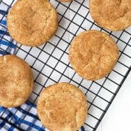 Image of snickerdoodles from a snickerdoodle recipe; image taken from above, six cookies pictured on a cooling rack with a blue and white towel underneath. Shot on a white background.