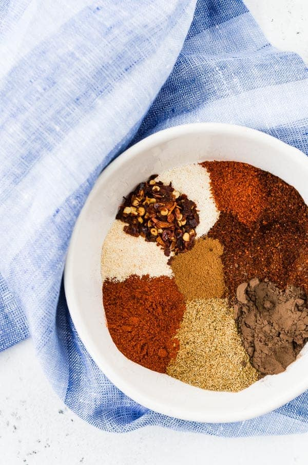 Spices in chili seasoning in a white bowl with a blue towel in the background.