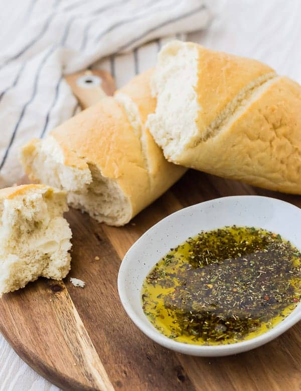 Oil with herbs and fresh bread on a wooden board with a striped towel in the background.