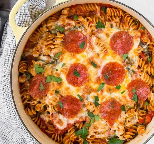 Image of pizza pasta with mozzarella cheese and pepperoni on top in yellow pan. Black spoon nearby.
