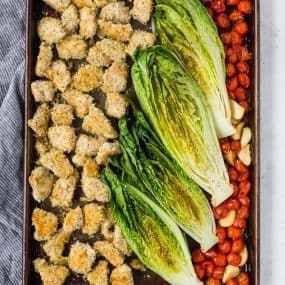 image of sheet pan dinner with crispy chicken, roasted romaine lettuce, and roasted tomatoes and garlic.