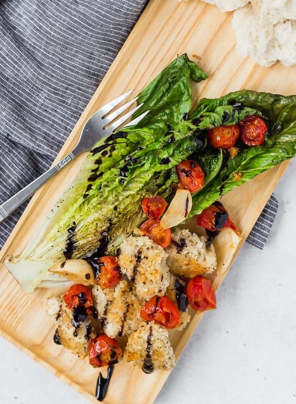 Image of Roasted Romaine salad with roasted tomatoes, roasted garlic, crispy chicken and balsamic glaze. Served on a wooden tray with a fork.