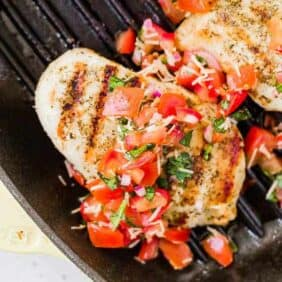 image of brushetta chicken with grill marks and bruschetta topping. Chicken is in a grill pan with two more chicken breasts.