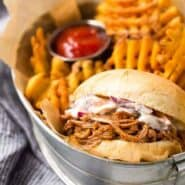 Photo of Instant Pot Pulled Pork on a bun with slaw and fries in a basket.