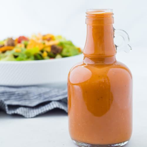 Image of homemade catalina dressing in a glass bottle with a taco salad in the background.