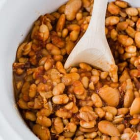 Image of crock pot baked beans in a white slow cooker with a wooden spoon stuck in the middle.
