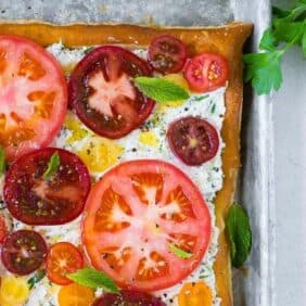 Image of herbed ricotta and fresh tomato tart, taken from above. Garnished with mint leaves.
