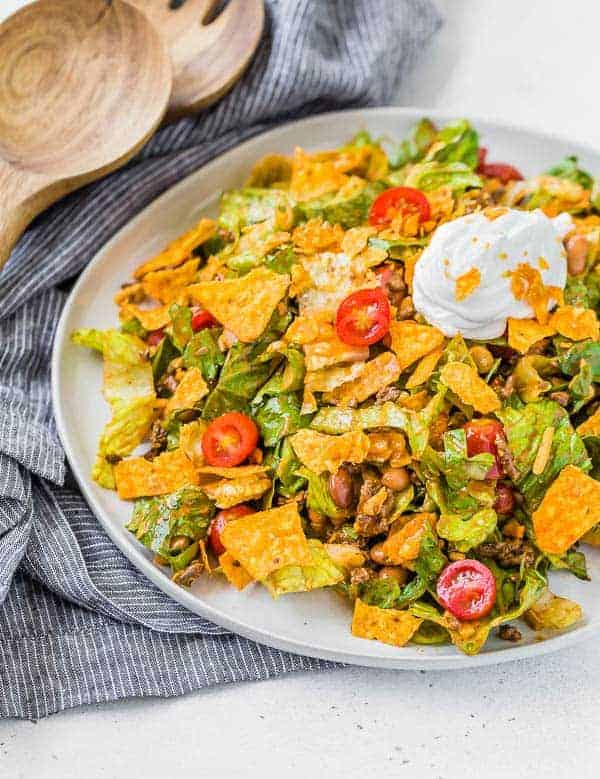 image of a classic taco salad recipe on a plate with a black and white linen and wooden serving utensils in the background of the photo.