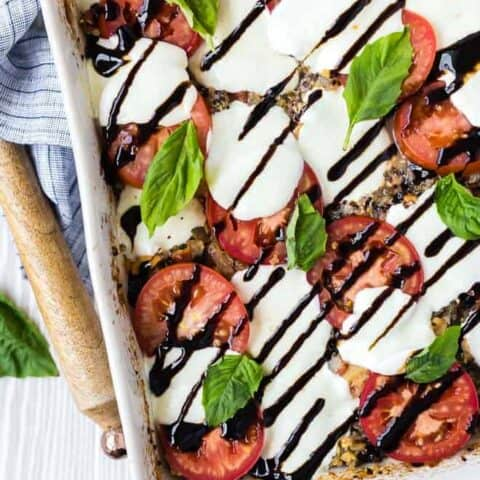 overhead image of caprese quinoa bake, sprinkled with fresh basil and drizzled with balsamic reduction. Wooden spoon and linen next to white baking dish.