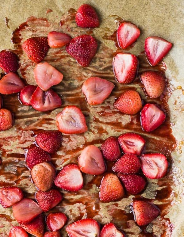 Roasted strawberries on a pan with parchment paper.
