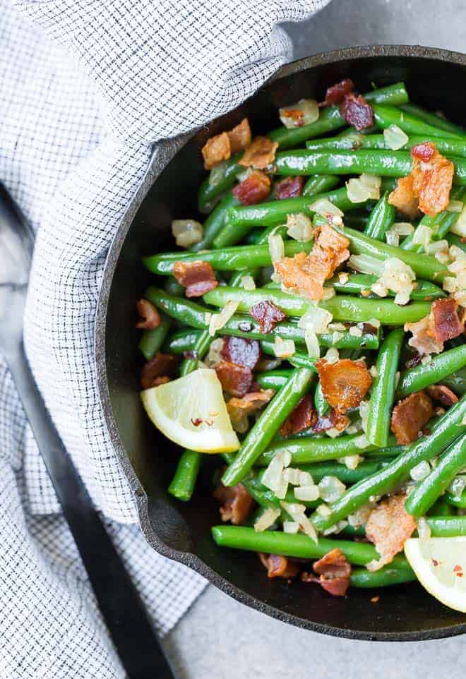 Image of vibrant green beans in a black cast iron skillet, sprinkled with garlic, onion, and bacon. Lemon wedges are used for garnish.