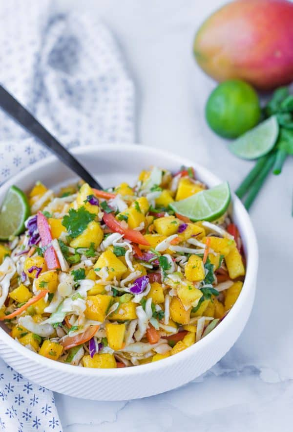 Image of mango slaw for tacos, in a white bowl with a mango and limes in the background