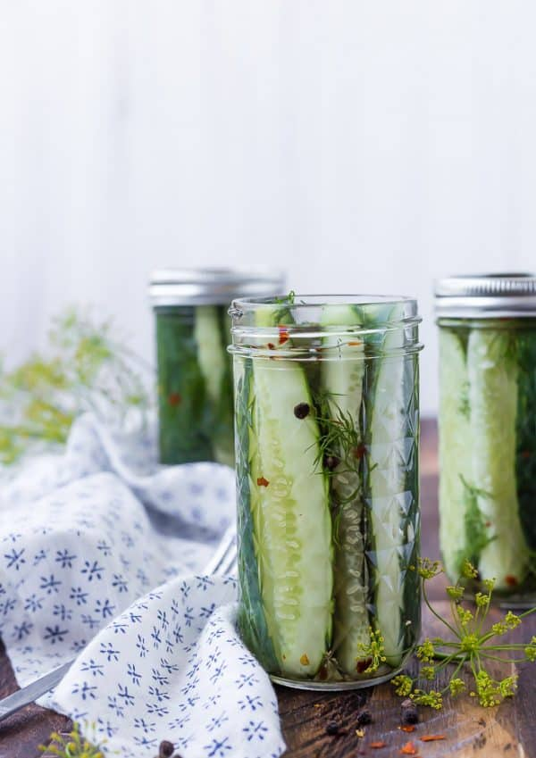 Image of quick dill pickles in a jar. Two pickle bars in the background are also pictured.